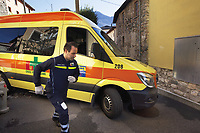 Switzerland. Canton Ticino. Dino. Day scene for a medical emergency intervention. A senior woman suffering from a broken ankle has to be brought to hospital by ambulance. A paramedic helps the ambulance's driver to get through the narrow streets. A sticker with the emergency phone number (144) to reach Ticino Soccorso. The man wears a blue uniforms and medical gloves. He works for theCroce Verde Lugano and is a volunteer specifically trained in emergency rescue. TheCroce Verde Lugano is a private organization which ensure health safety by addressing different emergencies services and rescue services. Volunteering is generally considered an altruistic activity where an individual provides services for no financial or social gain to benefit another person, group or organization. Volunteering is also renowned for skill development and is often intended to promote goodness or to improve human quality of life. Medical gloves are made of different polymers including latex, nitrile rubber, polyvinyl chloride and neoprene. 28.01.2018 © 2018 Didier Ruef