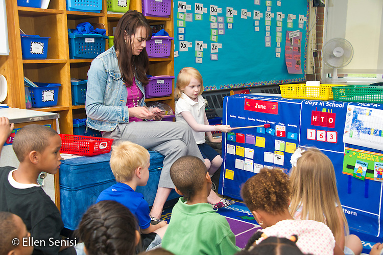 MR / Schenectady, NY. Zoller Elementary School. Kindergarten. A student (girl, 5) finds the current date on the calendar during teacher-led group lesson time. This is a daily, repetitive activity that helps students learn about and understand time. MR: San10, Sha11. ID: AL-gKs. © Ellen B. Senisi