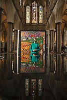 BNPS.co.uk (01202) 558833<br /> Pic: ZacharyCulpin/BNPS<br /> <br /> 8 million stitches, 1 Holy Exhibition<br /> <br /> Pictured: Reflected in the Cathedral's font - Salisbury Cathedral Verger, Kate Stubbings with an embroidery entitled,  'Goodbye to Eden'<br /> <br /> Twelve large embroidered panels fashioned from eight million stitches which tell the story of 'the Creation' have gone on display at Salisbury Cathedral.<br /> <br /> The panels, which measure up to 8ft by 11ft, are made from silk, hand-dyed materials, gold leaf and metallic leathers.<br /> <br /> They have been created by Devon-based textile artist Jacqui Parkinson who has dedicated three years to the solo project.<br /> <br /> The panels are inspired by the poetic verses of Genesis, the first book in the Bible, and include depictions of the Garden of Eden.