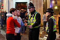 Police officers speak to two young men in Wind Street, Swansea, Wales  on Mad Friday, Booze Black Friday or Black Eye Friday, the last Friday night before Christmas Day, when traditionally people in the UK go out to celebrate the start of their holidays. Friday 22 December 2017
