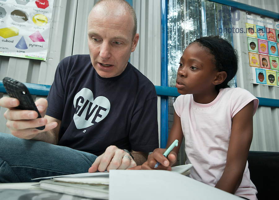 Mar. 13, 2013; Design professor Robert Sedlack tutors a girl at Kliptown Youth Project in Johannesburg, South Africa.<br /> <br /> Photo by Matt Cashore/University of Notre Dame