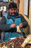 Peru, Cusco.  Woman Selling Fried Pork Snacks on the Street.