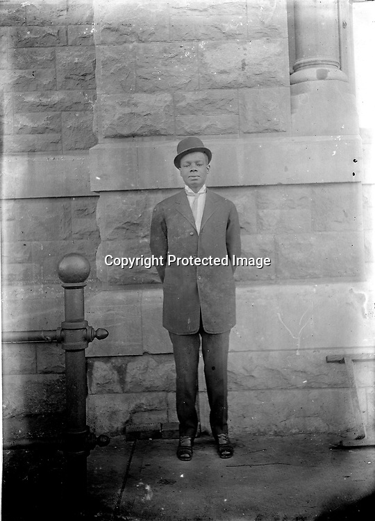 AT (OLD) CITY HALL. The stonework behind this gentleman and the metalwork beside him pinpoint his location alongside city hall, built in 1874-1879 as the U.S. courthouse and post office. It became Lincoln City Hall in 1905, when the new courthouse and post office was built just north of it on Government Square.<br /> <br /> Photographs taken on black and white glass negatives by African American photographer(s) John Johnson and Earl McWilliams from 1910 to 1925 in Lincoln, Nebraska. Douglas Keister has 280 5x7 glass negatives taken by these photographers. Larger scans available on request.