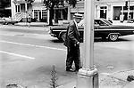 Nassau street, Princeton New Jersey USA 1969. An old man  crosses the street using a walking stick and  wearing a Panama hat.