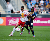Kenny Cooper (33) of the New York Red Bulls fights for the ball with Michael Lahoud (13) of the Philadelphia Union during the game at PPL Park in Chester, PA.  New York defeated Philadelphia, 3-0.