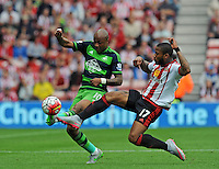 Jermain Lens of Sunderland (right) challenges Andre Ayew of Swansea City during the Barclays Premier League match between Sunderland and Swansea City played at Stadium of Light, Sunderland