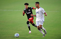 WASHINGTON, DC - AUGUST 25: Brandon Bye #15 of New England Revolution battles for the ball with Kevin Paredes #30 of D.C. United during a game between New England Revolution and D.C. United at Audi Field on August 25, 2020 in Washington, DC.