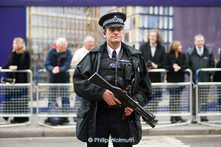 Police officer with a firearm.  Funeral of ex-Prime Minister Margaret Thatcher, City of London.