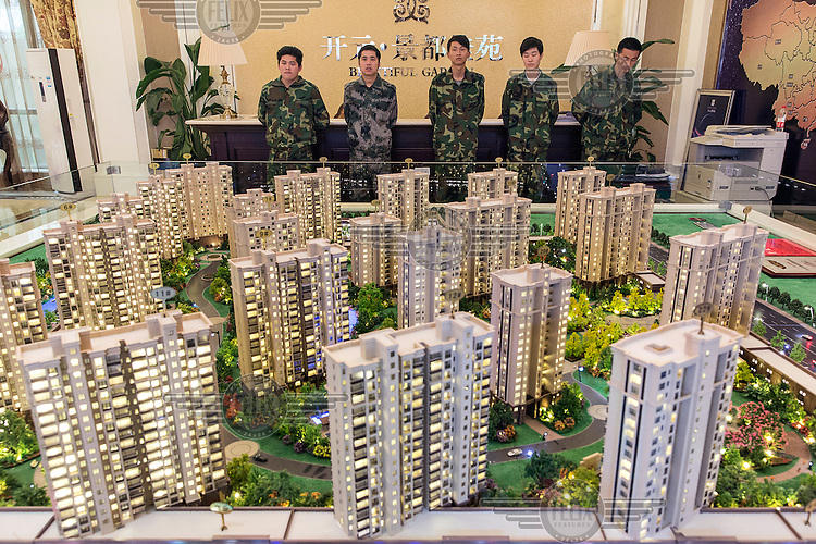 Security guards dressed in camouflage uniforms stand in one of the sales offices for a New Century Real Estate development in Taizhou. About 700 families bought into the company's Galaxy Noble Gardens development after it suddenly offered a 30 percent discount to new customers.