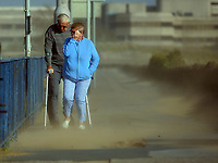 "Pictured: A couple struggle to walk against the strong wind and sand blasted from the beach on Oystermouth Road from the beach in Swansea, UK. Monday 16 October 2017<br /> Re: Remnants of Hurricane Ophelia are expected to bring strong gusts of wind to Wales when it hits Britain's shores.<br /> The hurricane, making its way from the Azores in the Atlantic Ocean, will have weakened to a storm when it arrives.<br /> A Met Office amber ""be prepared"" warning has been issued in some areas bringing ""potential danger to life""."