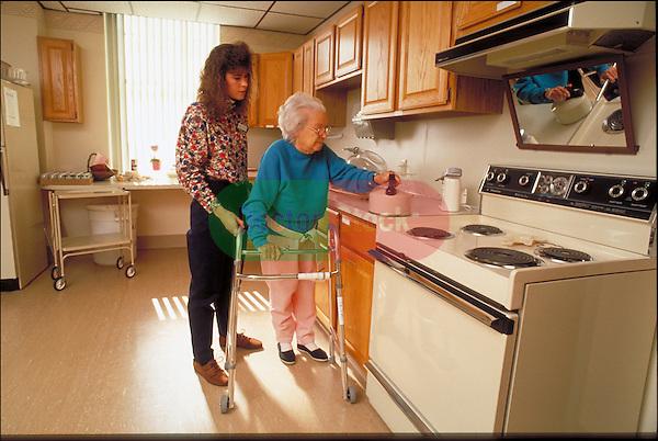 physical therapist helping elder woman in kitchen