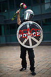 © Joel Goodman - 07973 332324 . 26/08/2017. Manchester , UK. A man wearing a costume in homage to a Banksy stencil , featuring use of decommissioned police riot shield and helmet . 2017 Pride parade through Manchester City Centre . The annual festival , which is the largest of its type in Europe , celebrates LGBT life . Photo credit : Joel Goodman