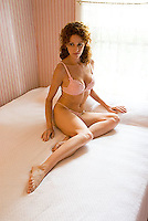 Woman wearing lingerie sitting in bed<br />