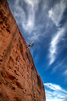 A canyoneer rappells down a sandstone cliff near St. George, Utah