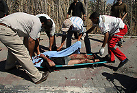 Palestinians evacuate the charred body of a man following an Israeli air strike on June 17, 2008 in Khan Yunis, southern Gaza Strip. Five people were killed and several others were wounded in the air strike near Qarara village east of the southern town of Khan Yunis, according to Muawiya Hassanein, the head of Gaza emergency services.photo by Ashraf Amrah