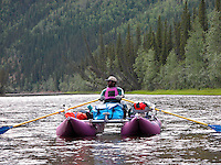 Charles Buckley floats past steep mountainsides along Alaska's Fortymile River.