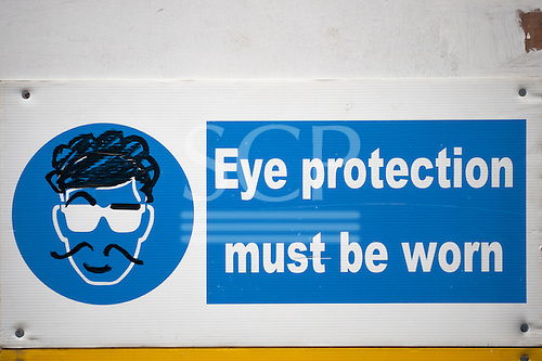 London, England. Eye protection sign with graffiti face with a raised eyebrow.