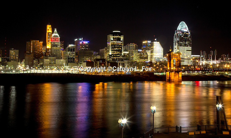 Lights illuminate the Cincinatti skyline as reflections show in the river.
