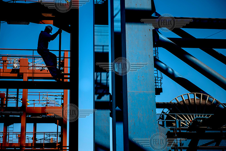 Third officer Lukas Buhring walks one of the gangways in between the containers on the Mary Maersk, the largest container ship in the world.