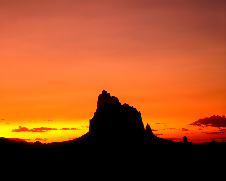 Sunset light on the silhouette of Shiprock; Navajo Nation, NM