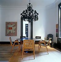 In the dining room of this New York apartment the chairs are 50s designs by Roland Ranier around a Belgian bluestone tabletop placed on a Saarinen base while the stunning black chandelier is a contemporary version of a Baccarat original