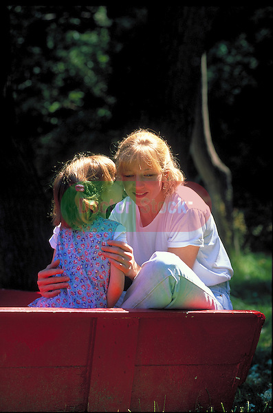 young girl kissing mother on park bench