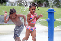 Three year old Kloe Rose (right) plays in the water feature with her cousin Izzy Rose, 6, Sunday in Belmont Park. Photo/Andrew Shurtleff Photography, LLC