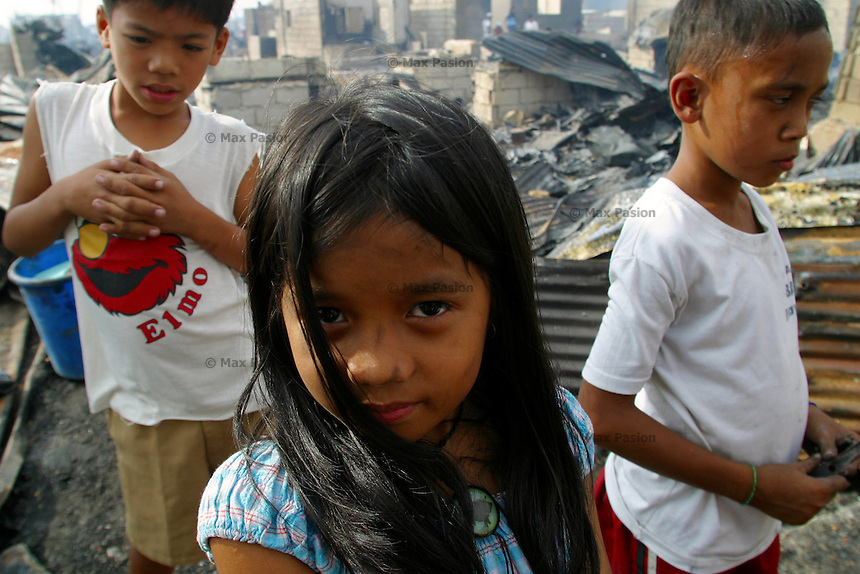 Children take a pause from scavenging after their shantytown called Baseco was razed by a fire that rendered more than 2,000 indigent families homeless. Miraculously, no one died in the conflagration. Tondo, Manila. 12 January 2004