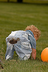 As a young toddler bends over he shows off the dirt on the back of his pants.