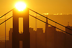The sun rose over the north tower of the Golden Gate Bridge with the San Francisco California in the background.