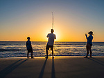Surf fishing in Florida at sunset on beach.