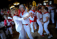 People dance in the casino of Pamplona after the fifth San Fermin Festival bull run, on July 11, 2012, in Pamplona, northern Spain. The festival is a symbol of Spanish culture that attracts thousands of tourists to watch the bull runs despite heavy condemnation from animal rights groups. (c) Pedro ARMESTRE