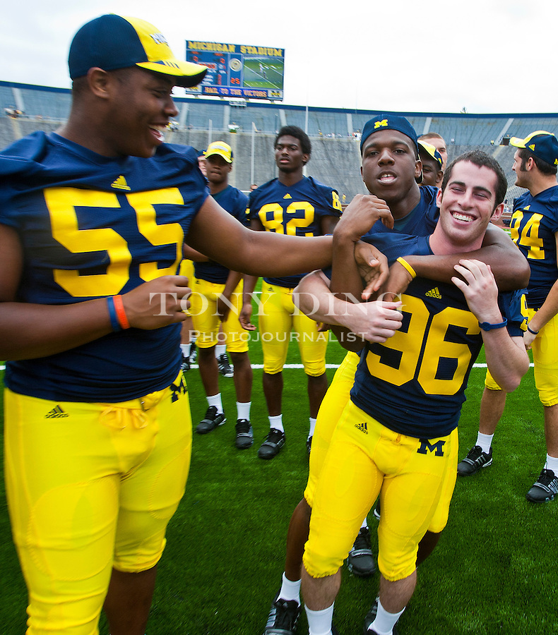 Michigan defensive end Jibreel Black (55) and safety Carvin Johnson (13) kid around with kicker Jeremy Ross (96), at the annual NCAA college football media day, Sunday, Aug. 22, 2010, in Ann Arbor, Mich. (AP Photo/Tony Ding)