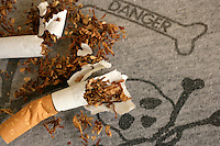 Torn up cigarette on fabric with danger and skull and crossbone