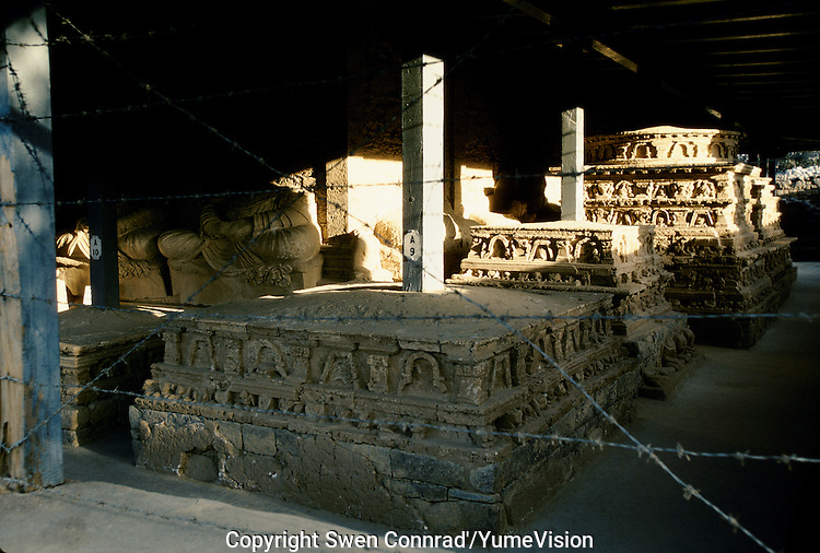 Sculpture of Buddha and Stupa's under barbed wire protection. View of the Takht-i-Bhai Buddhist Monastery in the Swat valley in Pakistan..Taxila, the main centre of Gandhara, is over 3,000 years old. Taxila had attracted Alexander the great from Macedonia in 326 BC, with whom the influence of Greek culture came to this part of the world. Taxila later came under the Mauryan dynasty and reached a remarkable matured level of development under the great Ashoka. During the year 2 BC, Buddhism was adopted as the state religion, which flourished and prevailed for over 1,000 years, until the year 10 AD. During this time Taxila, Swat and Charsadda (old Pushkalavati) became three important centers for culture, trade and learning. Hundreds of monasteries and stupas were built together with Greek and Kushan towns such as Sirkap and Sirsukh, both in Taxila.