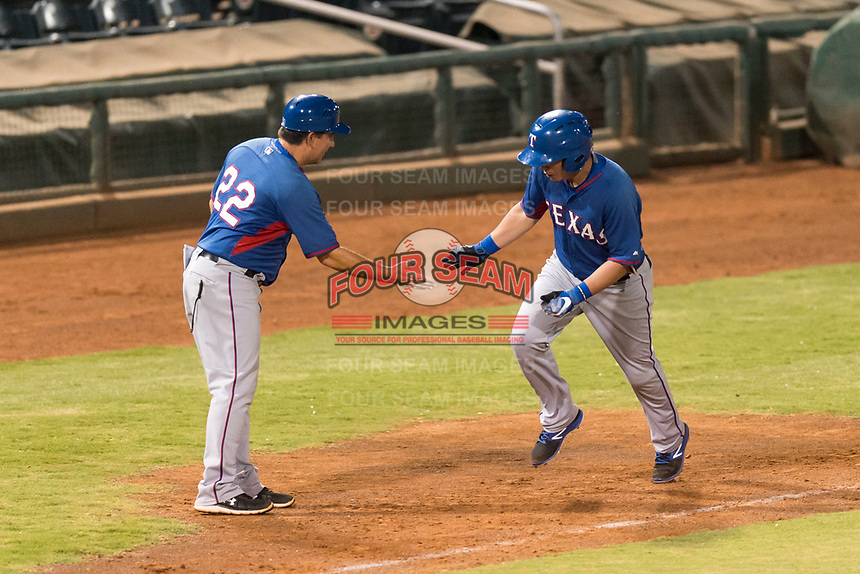 AZL Rangers right fielder Beder Gutierrez (8) is congratulated by manager Matt Siegel (22) as he rounds third base after hitting a two-run home run in the top of the 12th inning of an Arizona League playoff game against the AZL Indians 1 at Goodyear Ballpark on August 28, 2018 in Goodyear, Arizona. The AZL Rangers defeated the AZL Indians 1 7-4. (Zachary Lucy/Four Seam Images)