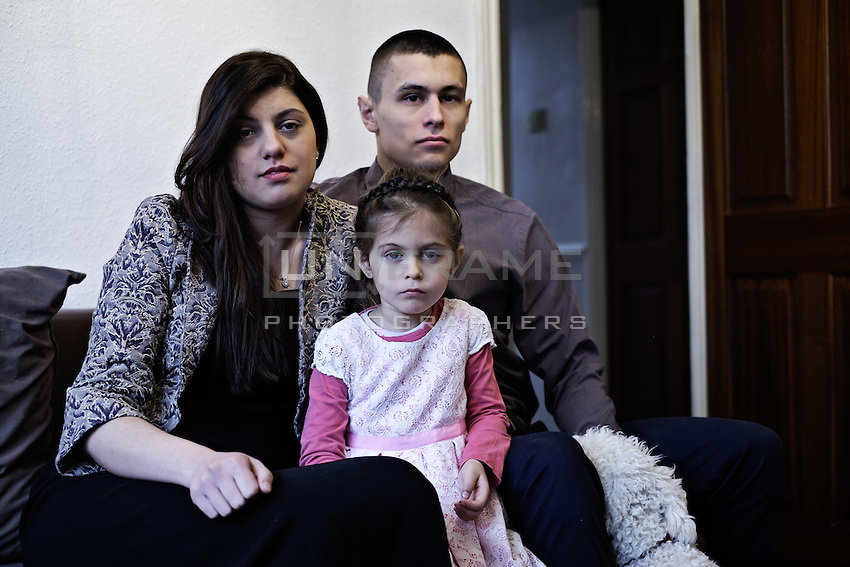 Przemek Kierpacz, his wife and his daughter pose in their home. London, UK, 9th March 2015.