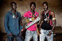 Members of a Muslim 'self-defence' group all draped with 'Gris Gris' amulets that confer good fortune and protection on their wearers. They are animist in origin but also worn by both Muslims and Christians throughout west and central Africa. The machete held by the man in the centre has an Arabic inscription that reads: 'Allahu Akbar' (God is Great).In late 2012 after years of instability and conflict, the Seleka, a predominantly Muslim rebel group, fuelled by grievances against the government, overran the country and, In March 2013, ousted President Francois Bozize, who fled the country. The rebel's leader Michel Djotodia was proclaimed president in August 2013. He disbanded the Seleka in September 2013 but law and order collapsed and ex-Seleka fighters roamed the country committing atrocities against the civilian population. In an attempt to defend their lives and property vigilante groups, calling themselves Anti-Balaka (Anti-Machete), formed to confront the ex-Seleka fighters but soon began to take reprisals against the wider Muslim population and the conflict became increasingly sectarian. By December 2013, with international fears of a genocide being voiced, French led peacekeepers deployed to the country began to act on a UN mandate to disarm the fighters and protect the civilian population. However, they have struggled to contain the situation. Much of the Muslim population, in particular, have been forced into ghettos where they are suffering from food shortages and limited access to healthcare. Often, only a few peacekeepers stand between them and a massacre by vengeful Anti-Balaka militants. UN reports describe 'thousands' killed, while over 600,000 people have been internally displaced and a further 200,000 have fled the county.