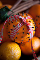 Detail of an orange decorated with cloves and a woven ribbon
