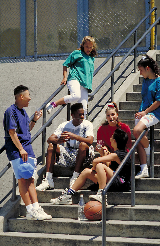 TEEN FRIENDS TAKE A BREAK FROM BASKETBALL. TEENS HANGING OUT. SAN FRANCISCO CALIFORNIA USA.