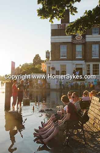 Richmond Upon Thames, Surrey, England Weekend visitors enjoy a drink at high tide.