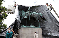 City of Charlottesville officials use a large tarp to cover up the Robert E. Lee statue Wednesday at Emancipation Park in Charlottesville, Virginia. Photo/The daily Progress/Andrew Shurtleff