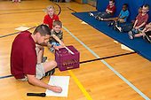 MR / Schenectady, NY. Zoller Elementary School (urban public school). Kindergarten inclusion classroom. Gym teacher records student's score on physical education assessment. While using teacher-made equipment to test student flexibility. This is part of his students' yearly assessment of their physical education skills. MR: Mel16, Ger2, Deg9. ID: AM-gKw. © Ellen B. Senisi.
