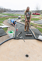 Terry Wallace (foreground) wirth Wallace Flooring smooths out newly attached artificial turf as Steve Kerstiens and Destiny Wallace work to trim the turf on one of the holes at the mini golf course at Kingsdale Play Ground in Bella Vista behind Riordan Hall. <br /> (NWA Democrat-Gazette/Spencer Tirey)