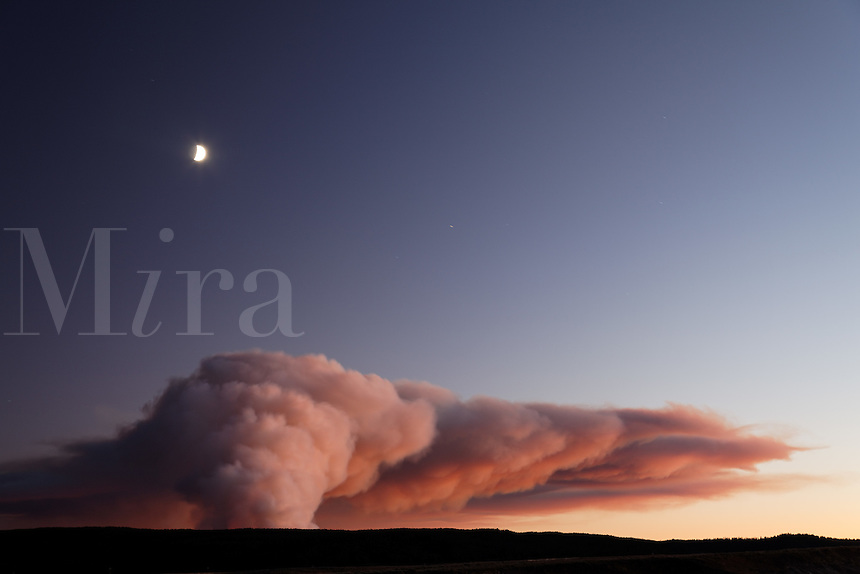 Smoke of forest fire burning on Central Plateau at sunset as viewed from Hayden Valley, September 24, 2009, Yellowstone National Park, Wyoming, USA