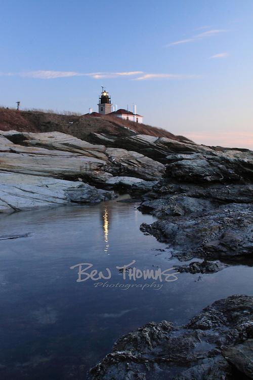 Tidepools reflect the Beavertail Lighthouse.
