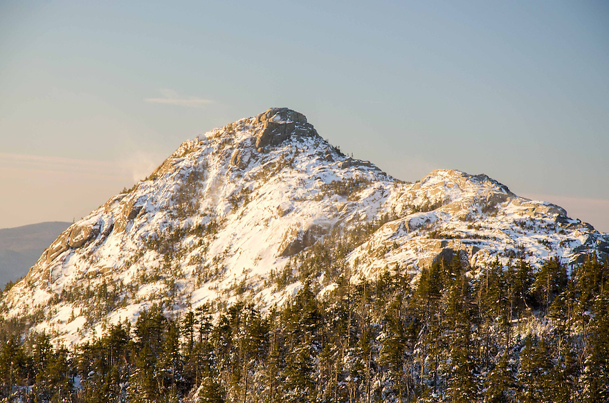 Golden sunlight bathes the frozen summit cone of Mt. Chocorua in this winter White Mountain landscape.