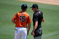 Bowie Baysox manager Buck Britton (15) talks with umpire Sean Shafer-Markle during an Eastern League game against the Binghamton Rumble Ponies on August 21, 2019 at Prince George's Stadium in Bowie, Maryland.  Bowie defeated Binghamton 7-6 in ten innings.  (Mike Janes/Four Seam Images)