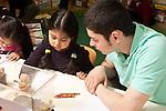 Education Preschool Headstart 3-4 children doing observational drawing of reptile turtle in aquarium girl and male teacher talking
