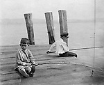 Lakewood NY: Two boys with stick poles fishing in Lake Chautauqua. Photographs were taken during a church field trip to Chautauqua Institution in New York (Lake Chautauqua). The Stewart family and friends visited Chautauqua during 1901 to hear Stewart's relative, Dr. S.H. Clark speak at the institute. Alice Brady Stewart chaperoned and Brady Stewart came along to photograph the trip.  The Gallery provides a glimpse of how the privileged and church faithful spent summers at Lake Chautauqua at the turn of the century.